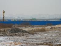 Забор стройки и бурильные установки