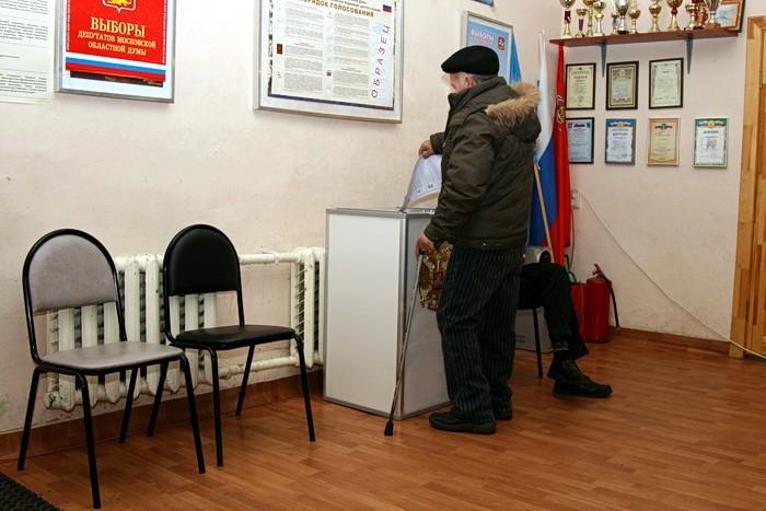 Избиратель опускает бюллетени в урну