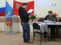 Наблюдатель изучает списки для голосования
